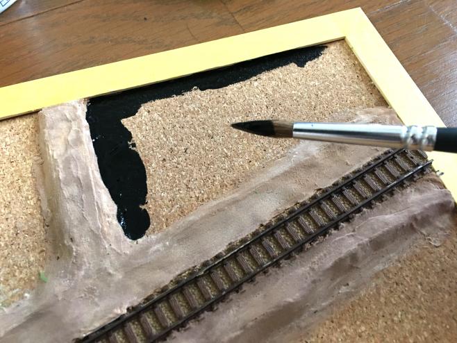 筆で塗ってゆきます。今回は「田んぼの境が見えた時に黒ければ目立たない、実物も暗く水があるから黒!」という点と、今後パウダーを撒く時にダンボールを保護する「防水」のためですので、こちらも大雑把に塗って大丈夫です。ただ、木枠とコルクの隙間にはきちんと塗料を塗って防水しておきましょう。