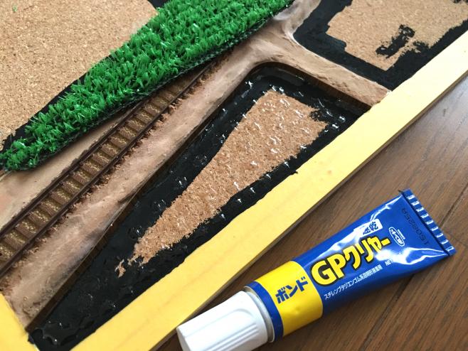 田んぼの接着にはゴム系接着剤を使い、全体に塗っておきます。切りだした「板」は先にゴム系接着剤で「土との境界」に接着してきましょう。