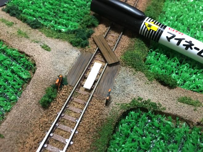 まず線路のあいだに高さを調整するため厚紙を両面テープで貼っておきます。厚紙に貼った木目シートは断面をマジックで塗り、目立たなくします。※完成後の工事のため、情景が大きく変わっておりますm(_ _)m