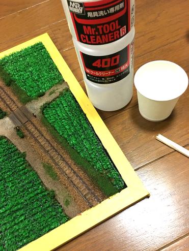 工具洗浄用のシンナーを紙コップなどに少しだけわけ、割り箸の先などに染み込ませます。綿棒や紙、布でも構いませんが、柔らかいものを使うとレールの左右などの塗料を落としたくない部分にも触れてしまうので、部員Iは割り箸を使っています。